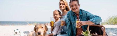 Photo pour Panoramic shot of family with glasses of orange juice sitting near golden retriever on beach - image libre de droit
