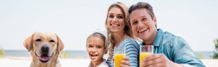 Photo for Horizontal crop of family looking at camera while holding glasses of orange juice near golden retriever on beach - Royalty Free Image