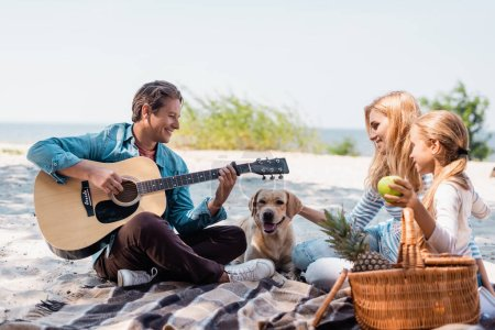 Photo pour Selective focus of man playing acoustic guitar near family and golden retriever on beach - image libre de droit