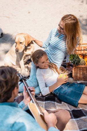 Overhead view of woman playing with golden retriever near daughter and husband with acoustic guitar on beach