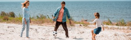 Photo pour Culture horizontale de la famille jouant au football sur la plage pendant le week-end - image libre de droit