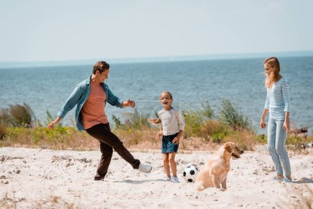 Photo pour Selective focus of man playing football with daughter near wife and golden retriever on beach - image libre de droit