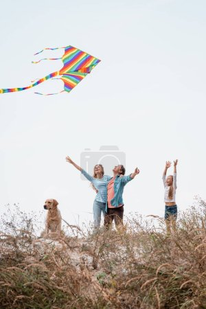 Photo pour Concentration sélective des parents avec cerf-volant embrassant près de la fille et golden retriever sur la colline herbeuse - image libre de droit