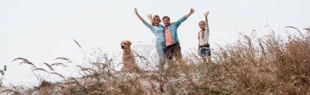 Photo pour Vue panoramique de la famille avec golden retriever agitant à la caméra sur une colline herbeuse - image libre de droit