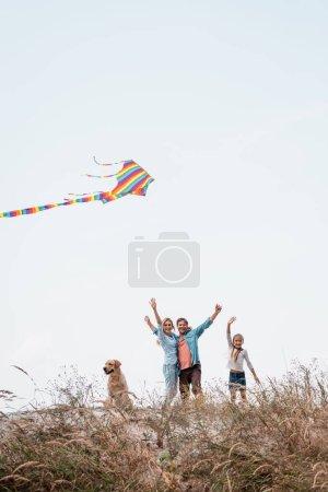 Photo pour Foyer sélectif de la famille avec golden retriever et cerf-volant agitant à la caméra sur la colline herbeuse - image libre de droit