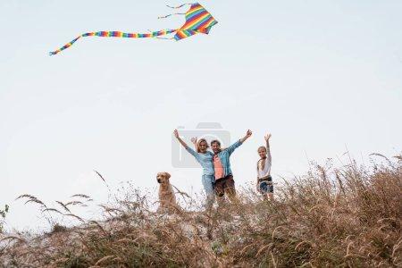 Photo pour Focus sélectif de la famille avec cerf-volant et golden retriever agitant les mains à la caméra sur la colline pendant le week-end - image libre de droit