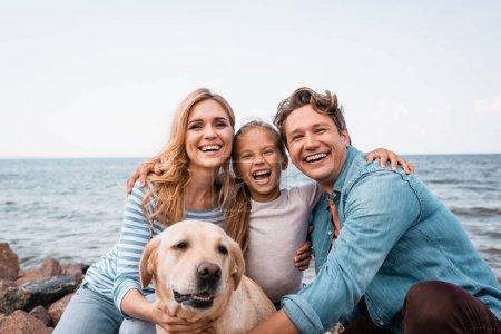 Photo pour Famille avec golden retriever regardant la caméra tout en embrassant sur la plage - image libre de droit