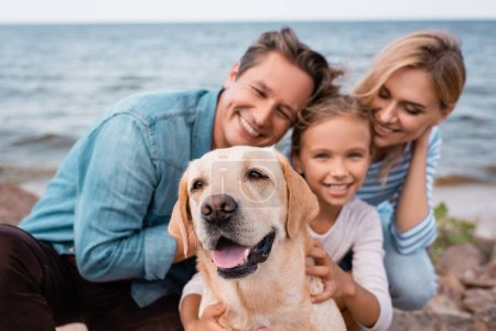 Photo for Selective focus of golden retriever sitting near family on beach - Royalty Free Image