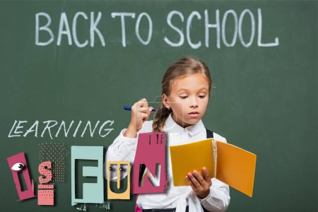 concentrated schoolgirl holding copy book and pen near chalkboard and learning is fun lettering in classroom