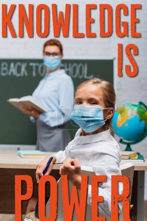 Photo pour Selective focus of schoolgirl in medical mask looking at camera while teacher standing near chalkboard and knowledge is power lettering - image libre de droit