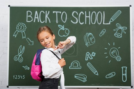 schoolgirl pointing with finger at backpack near chalkboard with back to school lettering and illustration