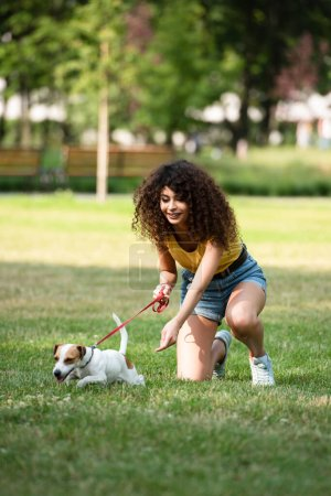 Selective focus of young woman keeping jack russell terrier dog on leash