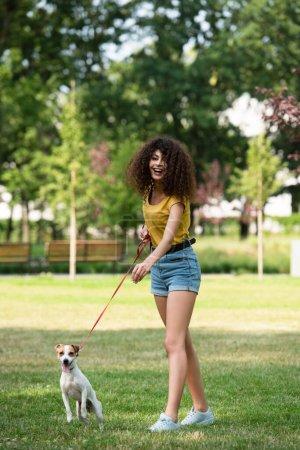 Selektiver Fokus der jungen Frau, die wegschaut und Hund an der Leine hält