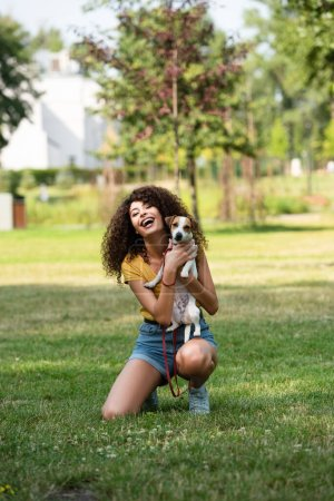 Selective focus of young woman holding jack russell terrier dog and laughing