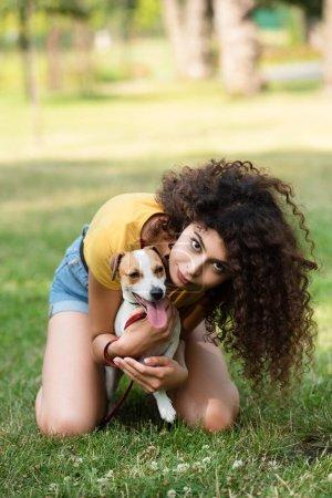 Photo pour Concentration sélective de la jeune femme assise sur l'herbe et embrassant chien - image libre de droit