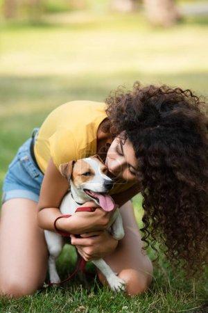 Selektiver Fokus einer jungen Frau, die auf Gras sitzt und Hund küsst