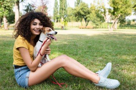 Photo pour Concentration sélective de la jeune femme assise sur l'herbe avec chien et regardant la caméra - image libre de droit