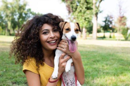 Selektiver Fokus einer jungen Frau mit Hund und Blick in die Kamera