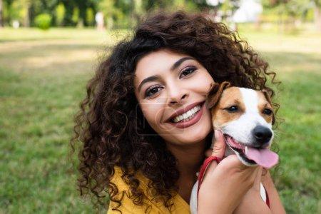Selektiver Fokus der fröhlichen Frau, die in die Kamera blickt und Hund hält
