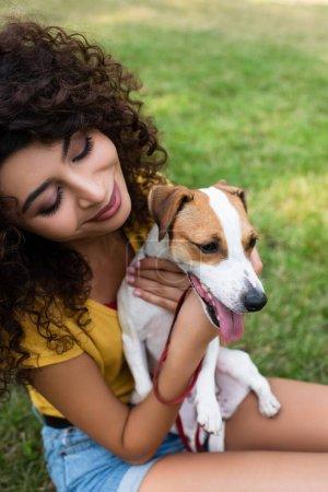 Photo pour Vue grand angle de la jeune femme assise sur l'herbe et regardant chien - image libre de droit