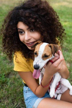 Photo pour Concentration sélective de la jeune femme tenant le chien et détournant le regard - image libre de droit