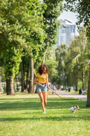 Selective focus of young woman walking with jack russell terrier dog in park