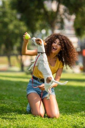 Photo pour Focus sélectif de femme excitée jouant à la balle de tennis avec chien - image libre de droit