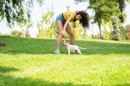 Photo pour Concentration sélective de la jeune femme avec Jack Russell terrier chien sur l'herbe - image libre de droit