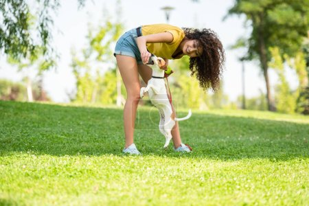 Selective focus of young woman playing with jumping dog in park