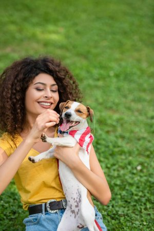 Photo pour Concentration sélective de la jeune femme assise et tenant le chien avec bandana drapeau américain - image libre de droit
