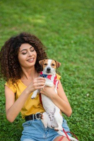 Photo pour Concentration sélective de la jeune femme montrant chien à la caméra avec bandana drapeau américain - image libre de droit