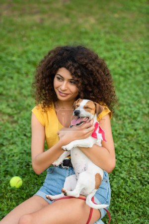 Selective focus of young woman sitting on grass with dog and looking away