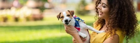 Photo for Horizontal crop of young woman holding and looking at jack russell terrier dog - Royalty Free Image