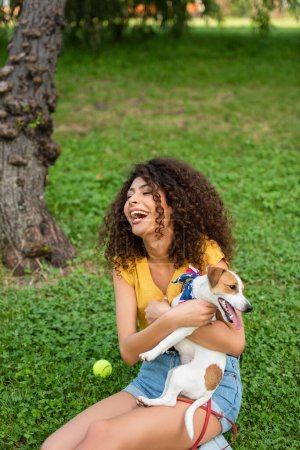 Selective focus of excited woman sitting with jack russell terrier dog on grass