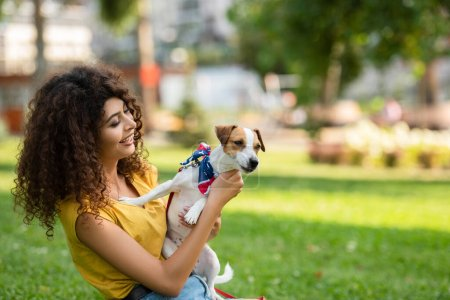 Selective focus of young woman on grass with dog in american flag bandana