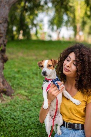Photo pour Concentration sélective de la jeune femme tenant le chien portant bandana drapeau américain - image libre de droit