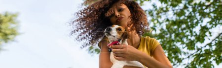 Photo for Low angle view of curly woman making duck face while holding jack russell terrier dog against blue sky, panoramic crop - Royalty Free Image