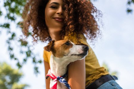 Photo for Low angle view of joyful, curly woman holding jack russell terrier dog - Royalty Free Image
