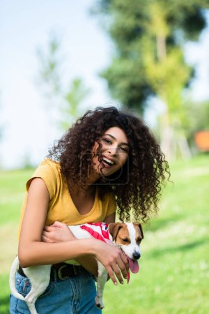 curly woman looking at camera and laughing while holding jack russell terrier dog