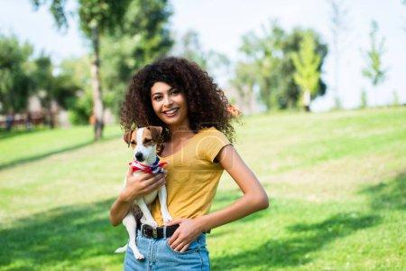 Photo pour Jeune femme en tenue d'été debout avec la main dans la poche tout en tenant Jack Russell terrier chien dans le parc - image libre de droit