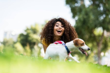 selective focus of excited woman laughing and looking at camera while lying on grass near jack russell terrier dog