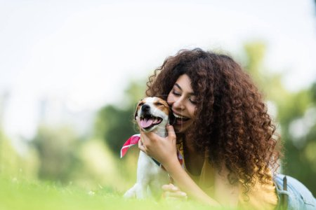 Photo pour Foyer sélectif de excité, femme bouclée étreignant Jack Russell terrier chien tout en étant couché sur l'herbe - image libre de droit
