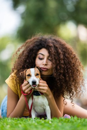 Photo for Brunette, curly woman pouting lips while relaxing with jack russell terrier dog on green grass - Royalty Free Image