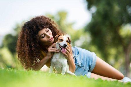 Photo pour Vue de niveau de surface de jeune femme bouclée embrassant Jack Russell Terrier chien tout en étant couché sur la pelouse verte - image libre de droit