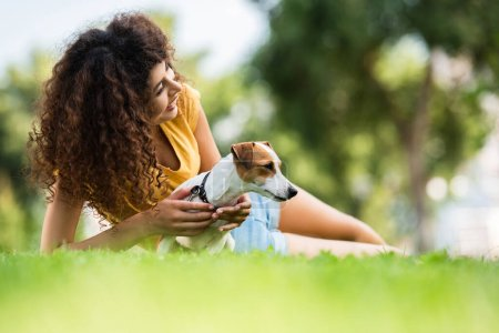 selective focus of curly woman looking away and laughing while lying on lawn with jack russell terrier dog
