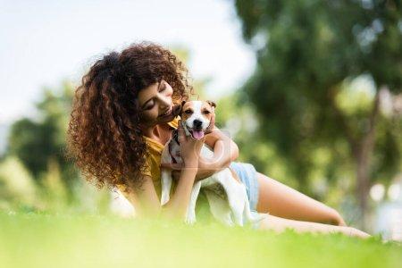 enfoque selectivo de la mujer alegre abrazo gato russell terrier perro mientras está acostado en el césped