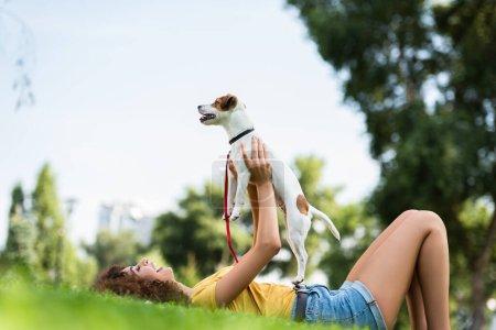 Photo pour Vue de niveau de surface de la femme excitée en tenue d'été tenant Jack Russell Terrier chien tout en étant couché sur l'herbe dans le parc - image libre de droit