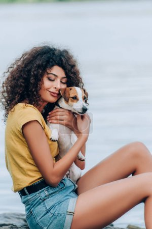 Photo for Young woman in summer outfit cuddling jack russell terrier dog with closed eyes near lake - Royalty Free Image