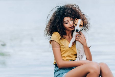 curly woman in summer outfit hugging jack russell terrier dog near lake