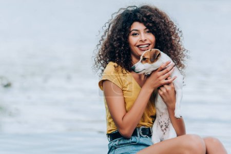excited, curly woman in summer outfit embracing jack russell terrier dog near lake